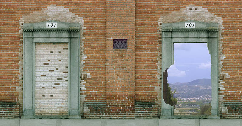 Minibanner: A brick wall with two doors, one blocked by bricks, the other opening onto a blue sky and green hills.