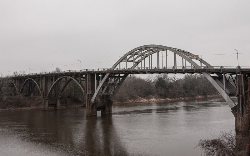 The arches of the Edmund Pettus Bridge seen from the east bank, a few hundred yards downstream.