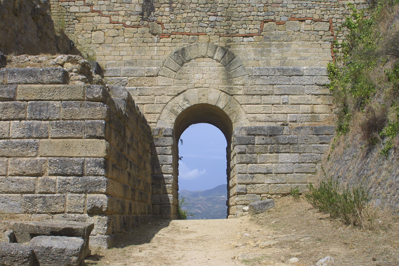 photo of an arched passageway in a stone wall, revealing a view of distant hills and sky